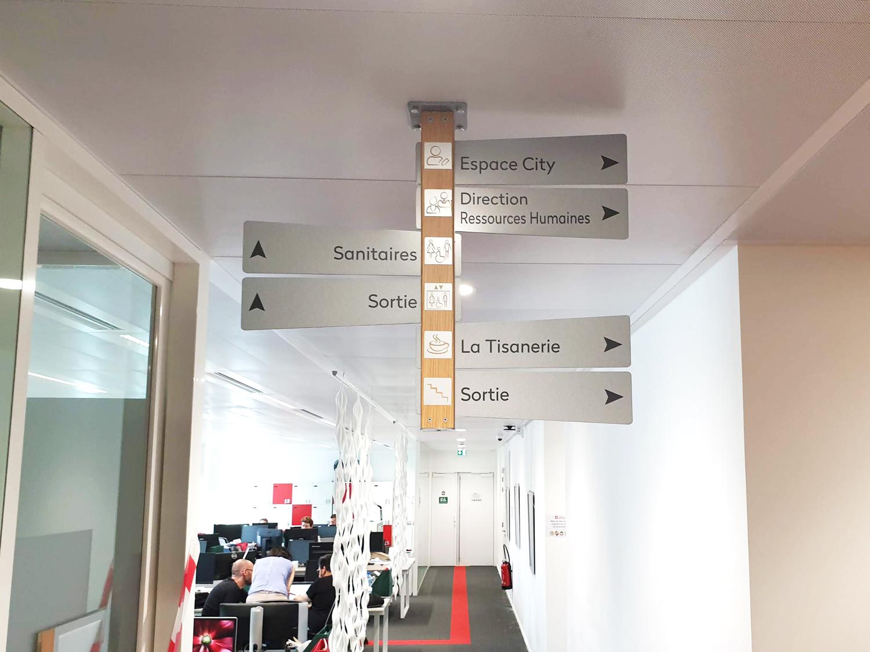 Signalétique d'orientation suspendue, structure en aluminium, film adhésif aspect bois et textes en film adhésif teinté masse
